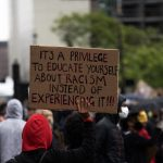 Sign reads: It's a privilege to educate yourself about racism instead of experiencing it